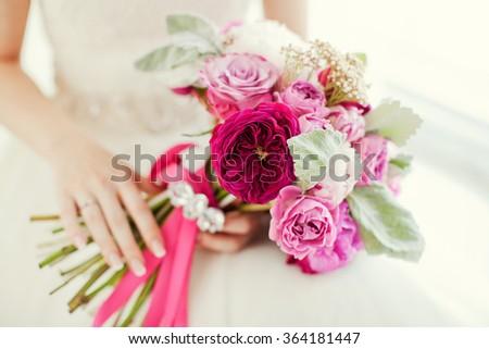 Beautiful pink bouquet in bride's hands - stock photo