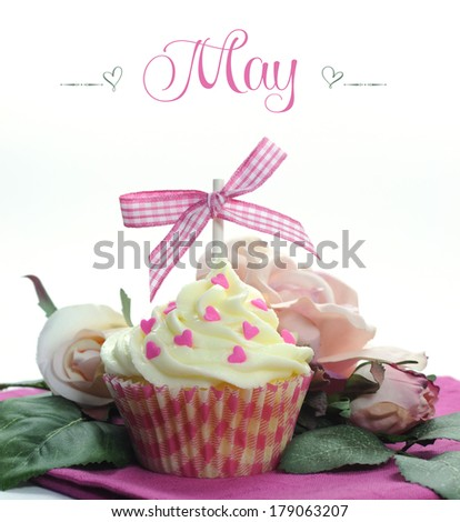 Beautiful pink heart or Mothers Day theme cupcake with seasonal flowers and decorations for the month of May with sample text or copy space for your text here. - stock photo
