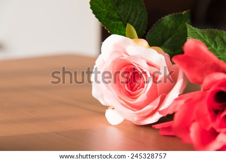 Beautiful pink rose on wooden table - stock photo