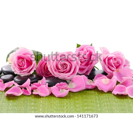 Beautiful pink roses arranged with stones on green mat - stock photo