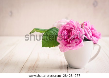 Beautiful pink tea roses on a white wooden background. Romantic background. Vintage shabby frame - stock photo