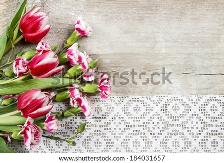 Beautiful pink tulips and carnations on wooden background - stock photo