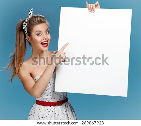 Beautiful pinup girl shows forefinger on the blank banner / photo set of young American pin-up model on blue background with space for text - stock photo