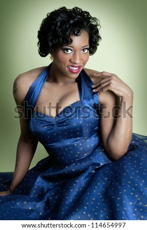 Beautiful pinup model wearing fancy blue dress - stock photo