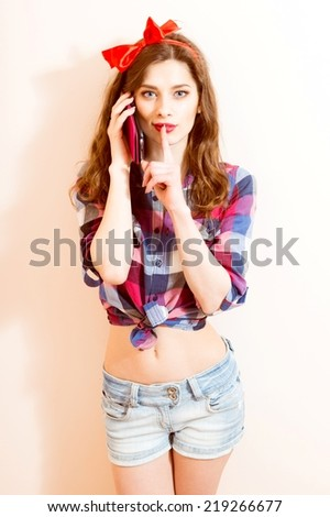 beautiful pinup young woman girl with red lipstick looking at camera on mobile cell phone - stock photo