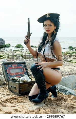 Beautiful pirate woman sitting near treasure chest on the beach with a classic pistol in her hand - stock photo