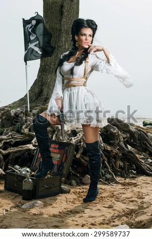 Beautiful pirate woman standing near treasure chest on the beach - stock photo