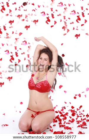 Beautiful playful brunette woman playing with red falling rose petals sitting on white isolated background wearing sexy red lingerie underwear - stock photo