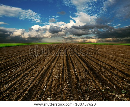 Beautiful plowed field and cloudy sky scene - stock photo