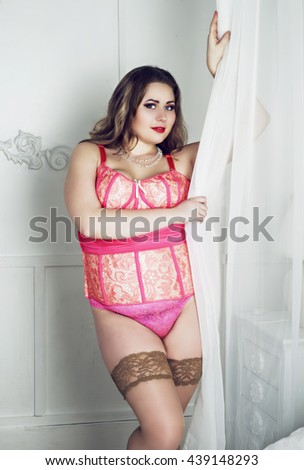 beautiful plus size model wearing lingerie in bedroom - stock photo