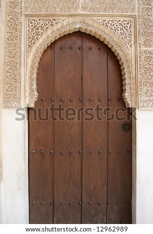 Beautiful portal wirth closed door to the ancient palace Alhambra in Spain - stock photo