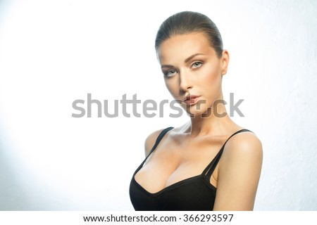 Beautiful portrait of a girl of European appearance with big breasts, wearing a black t-shirt - stock photo