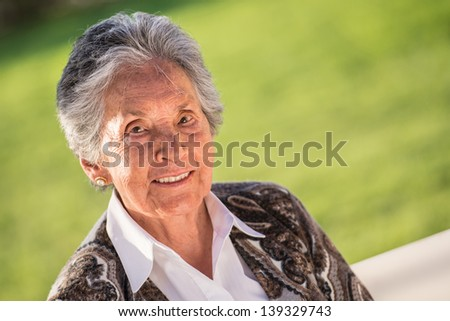 Beautiful portrait of a senior woman smiling outdoors - stock photo