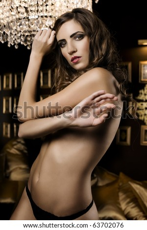 beautiful portrait of a sexy woman in a luxury room with black and gold color - stock photo