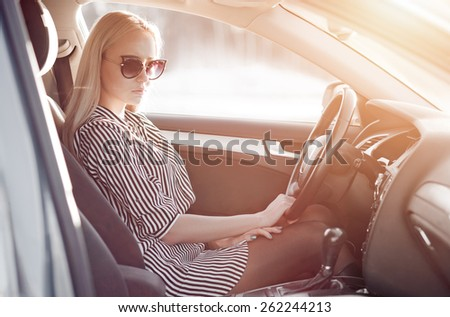 Beautiful portrait of blondie young lady at the wheel of sport car - stock photo