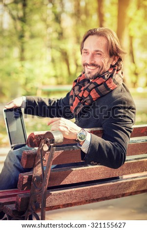 Beautiful portrait of middle-aged man resting on the bench outdoors. Happy man holding tablet PC and smiling for the camera. - stock photo