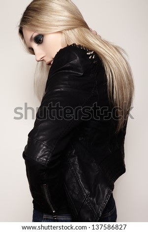 Beautiful portrait of rock woman model in leather jacket with dark evening make-up. Perfect street fashion. Punk clothes with spikes - stock photo