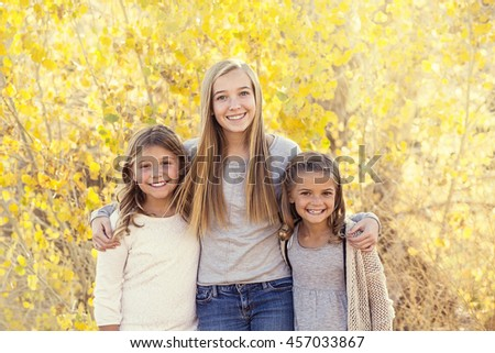 Beautiful Portrait of smiling happy kids outdoors. Three sisters standing together for a cute picture on a warm fall day - stock photo