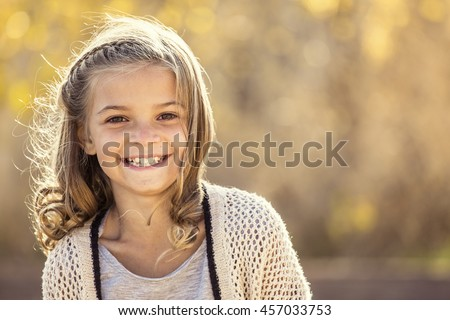 Beautiful Portrait of smiling little girl outdoors. Taking a cute picture on a warm fall day - stock photo