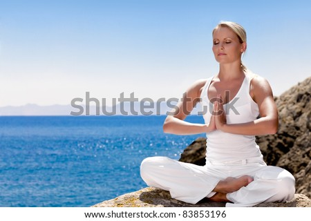 Beautiful positiveblond girl clothing in white sit at the seaside on the rock and meditating in yoga pose - stock photo