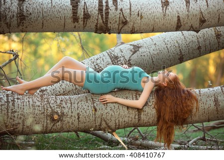 Beautiful pregnant fashion model lying and posing among trees, outdoor in nature. - stock photo