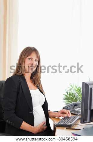 Beautiful pregnant female working with a computer at the office - stock photo