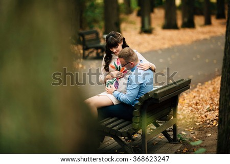 Beautiful pregnant stylish couple relaxing outside in the autumn park sitting on bench. They are lovely looking at belly. - stock photo