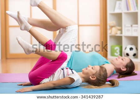 Beautiful pregnant woman and child daughter at gym fitness exercise practicing aerobics on mat - stock photo