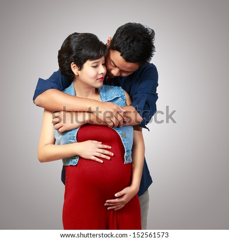 Beautiful pregnant woman and her husband - stock photo