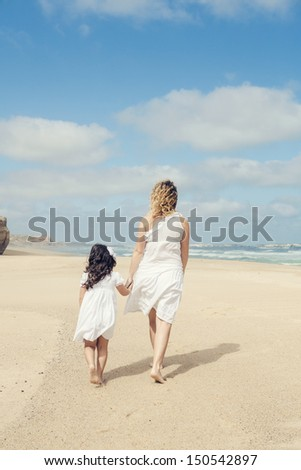 Beautiful pregnant woman and her little daughter walking on the beach - stock photo