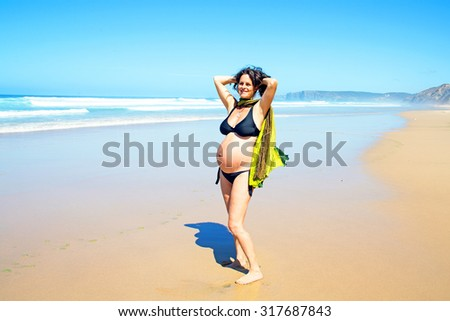 Beautiful pregnant woman at the beach - stock photo