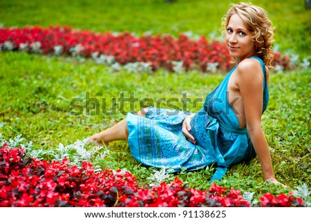 Beautiful pregnant woman having rest on green grass in park and - stock photo