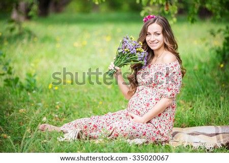 Beautiful pregnant woman holding flowers outdoors in summer park - stock photo