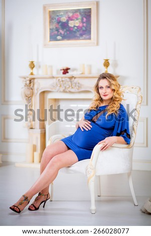 Beautiful pregnant woman in a luxury evening blue dress sits on a chair. - stock photo