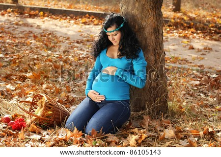 Beautiful pregnant woman in autumn park, outdoors - stock photo