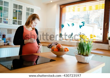 Beautiful pregnant woman in kitchen holding her belly - stock photo