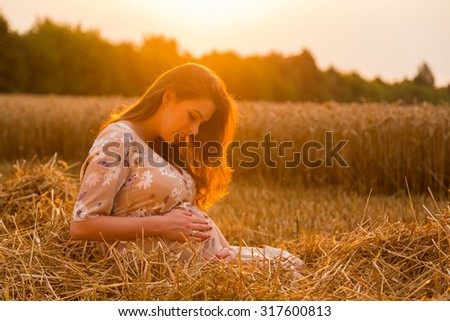 Beautiful pregnant woman in the sunset - stock photo