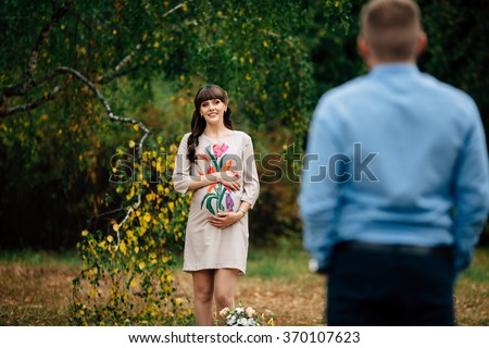 Beautiful pregnant woman is standing lovely on the green lawn with her hand on belly and looking at her handsome husband in autumn park.  - stock photo