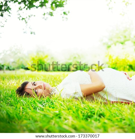 Beautiful Pregnant Woman lies on the Grass in sunlight and touching her belly, outdoor, pregnancy as natural process - stock photo