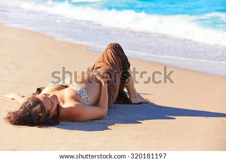 Beautiful pregnant woman on the beach lying on sand - stock photo