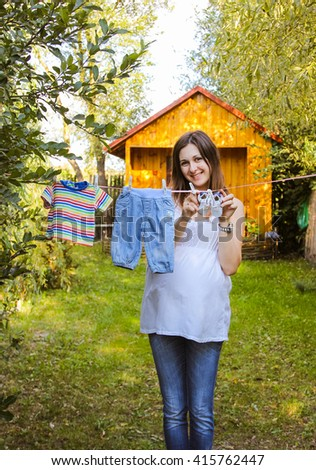 Beautiful pregnant woman outdoor hanging childrens clothes. Great time. Family comfort near house - stock photo