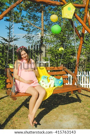 Beautiful pregnant woman outdoor with decorations. Great time. Family comfort and warm rays of the sun. - stock photo