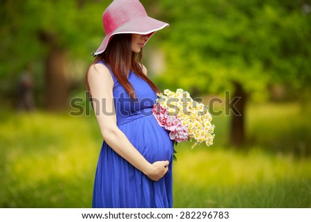 Beautiful Pregnant Woman outdoors with flowers pregnant girl portrait, healthy pregnancy, pregnant young female in park summer, soft focus. series - stock photo