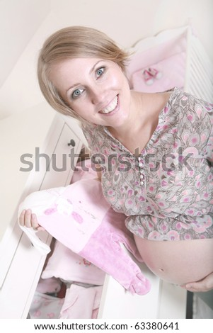 beautiful pregnant woman prepares for the baby - stock photo