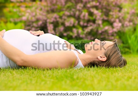 Beautiful pregnant woman relaxing on grass - stock photo