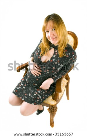 beautiful pregnant woman sits on chair on white background - stock photo