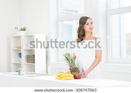 Beautiful pregnant woman washing a pineapple. - stock photo