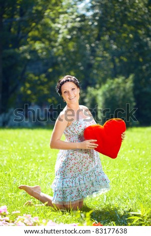 Beautiful pregnant woman with a red heart in hands - stock photo