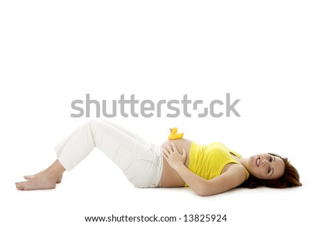 Beautiful pregnant woman with a rubber duck on her tummy - stock photo