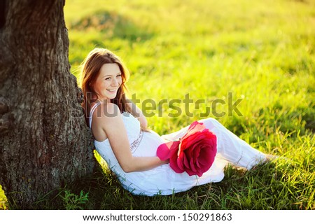 beautiful  pregnant woman with big red flower  posing in garden, toothy smile - stock photo